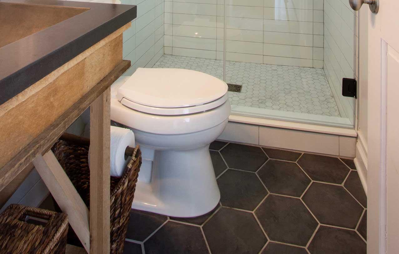 Brown hexagonal floor tiles with toilet and counter in view