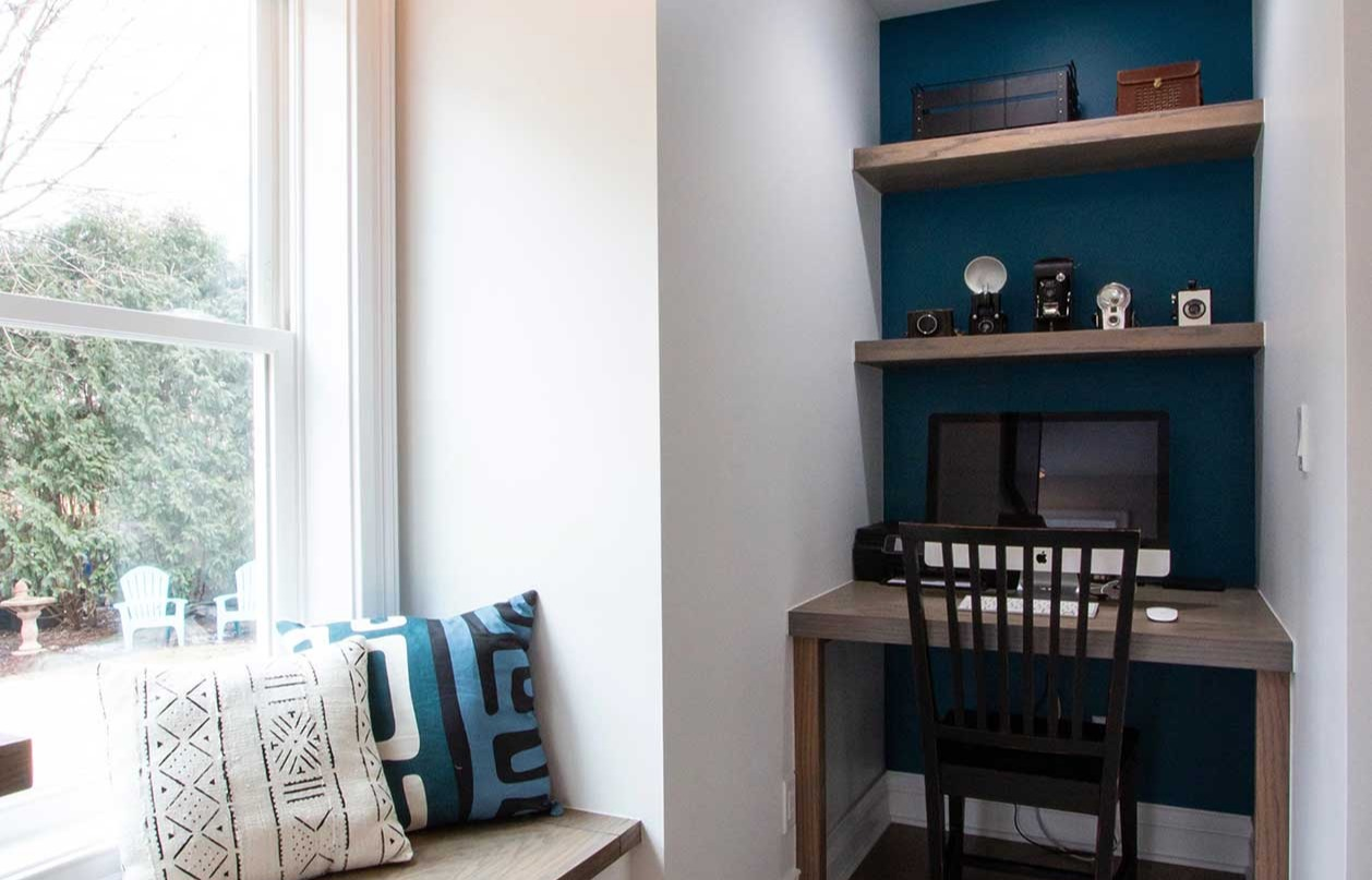 Window seat with white and blue pillows by desk and chair