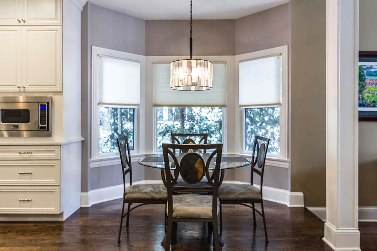 central dining area with hanging glass light and bay area windows