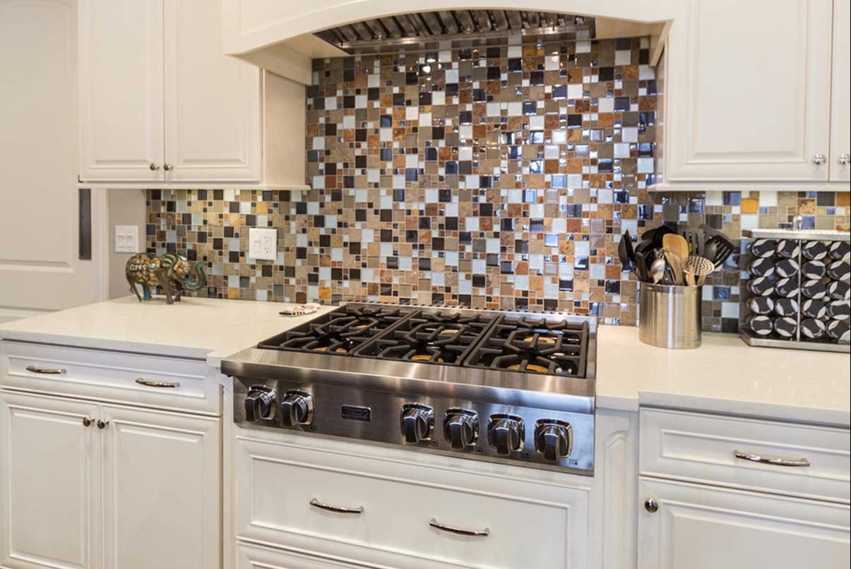 multi-color kitchen backsplash with white counter and cabinets