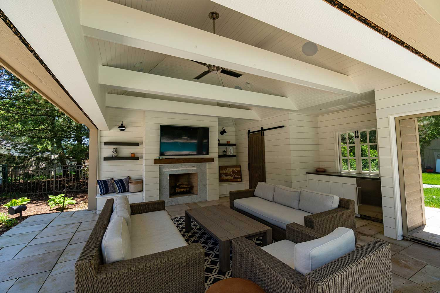 Seating area inside pool shack in front of stone fireplace