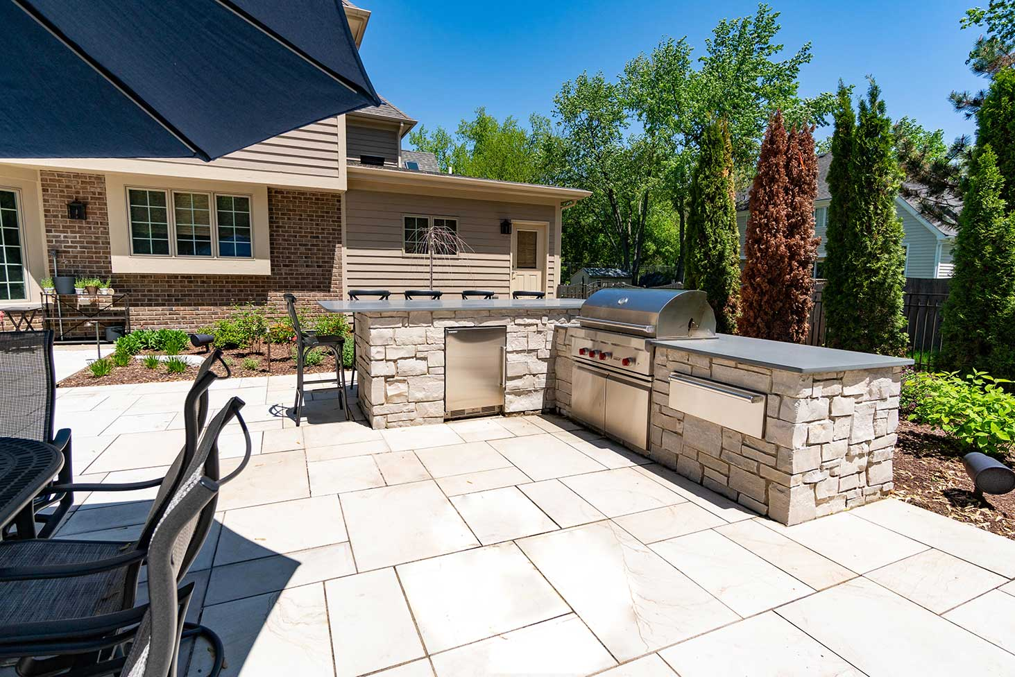 Pool house patio with stone grill and umbrella