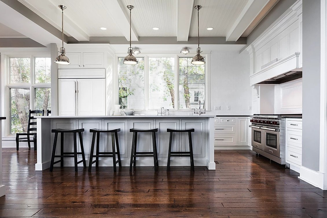 Kitchen counter with black stools and silver overhead lamps